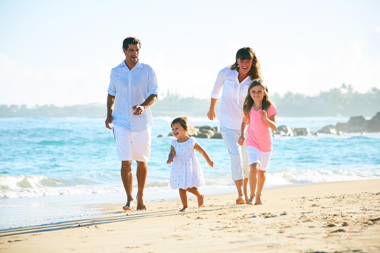 family runs along the beach